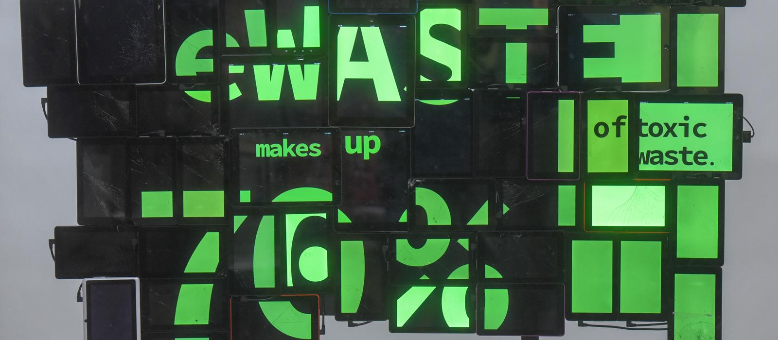 "A photo of an art installation made up of recycled iPads, and other similar devices with neon green and black imagery indicating that ""eWaste makes up 70% of toxic waste."""