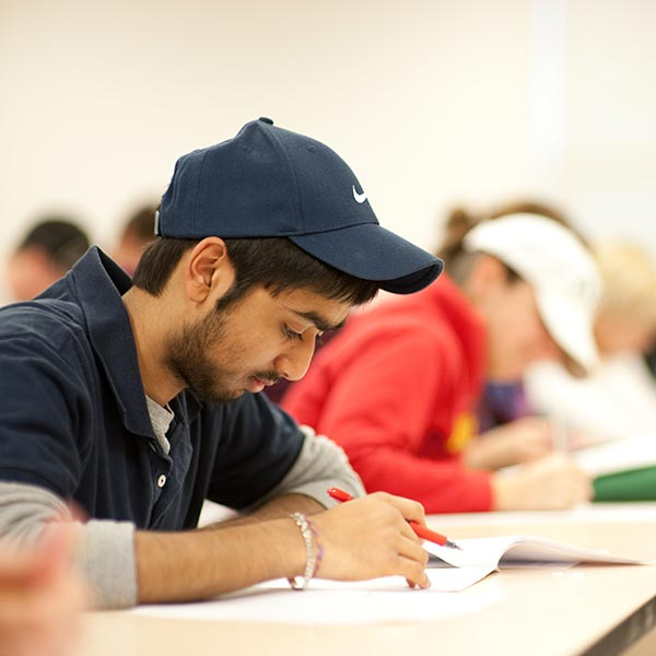 A student in a hat taking notes