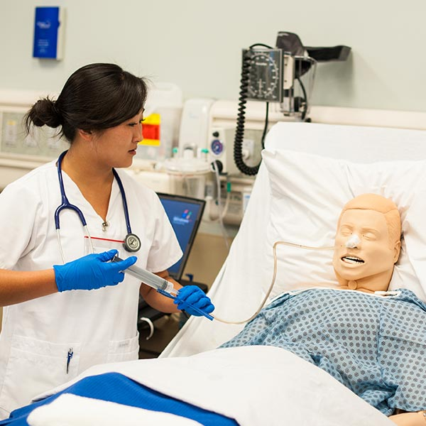 A nursing student taking vitals on a human simulator