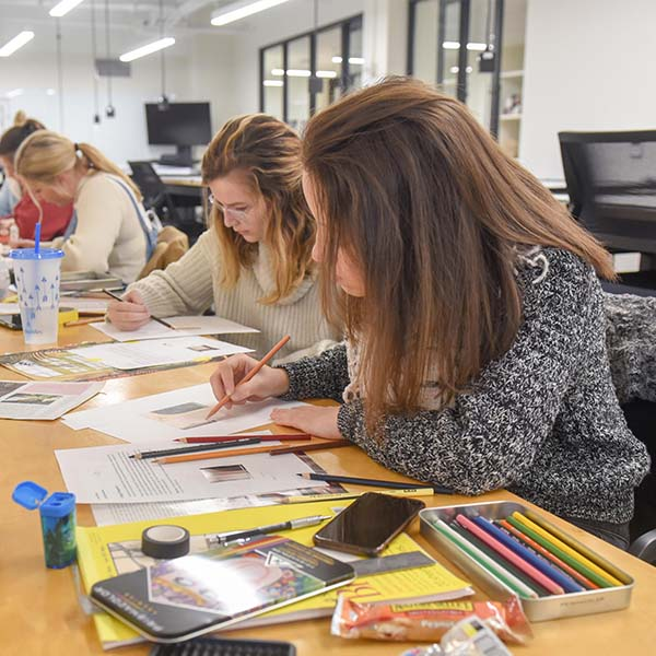 Two interior design students working on blueprints in a studio